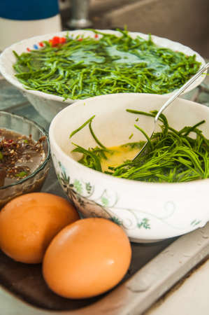 cha om: egg in green acacia pennata in white bowl Stock Photo