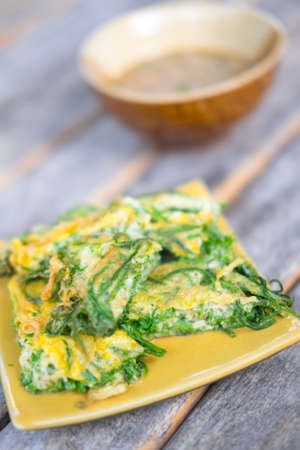pennata: Fried acacia pennata omelet on the wooden background, Thai Cuisine Stock Photo