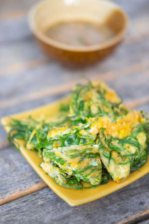 Fried acacia pennata omelet on the wooden background, Thai Cuisine Stock Photo