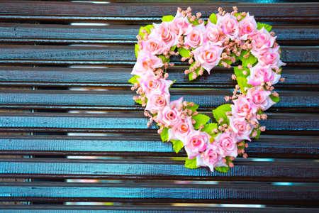 Rose flower heart on wooden background