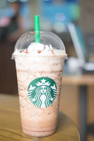Samutprakarn, Thailand - May 21, 2016: large iced Starbucks drink in a clear cup on a black table with blurred background inside Home Pro Village , Suvarnabhumi shopping mall