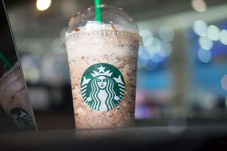 Samutprakarn, Thailand - May 21, 2016: large iced Starbucks drink in a clear cup on a black table with blurred background inside Home Pro Village , Suvarnabhumishopping mall Editorial