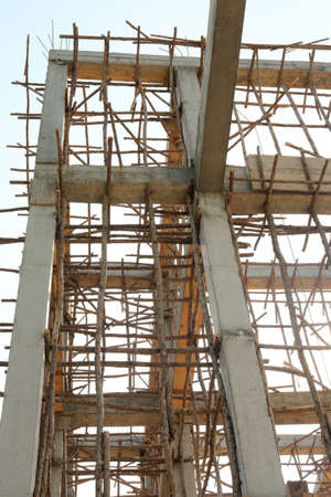 bracing: Timber beam formwork supported by row of scaffolding in construction site
