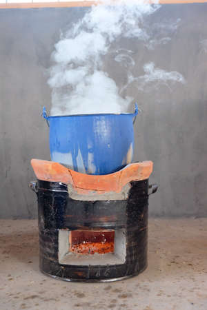 evaporating: steel pot on clay stove in thai kitchen