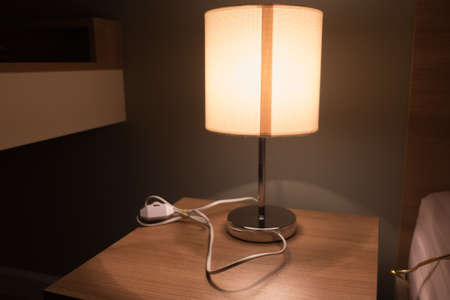 night table: Lamp on a night table next to a bed