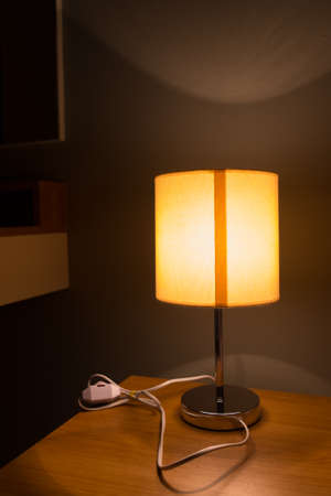 bedside: Modern table lamp on a bedside table, lamp is on Stock Photo