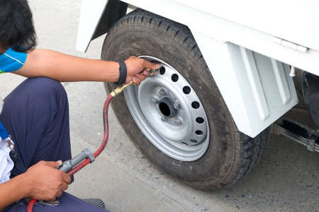 air pressure: Man checking air pressure and filling air in the tires of his car