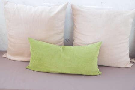white sofa: Green and white pillows on leather sofa Stock Photo