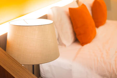 orange pattern pillows on classic style bed and reading lamp on bedside table Stock Photo
