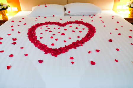 Wedding bed topped with rose petals, Thai style wedding 免版税图像