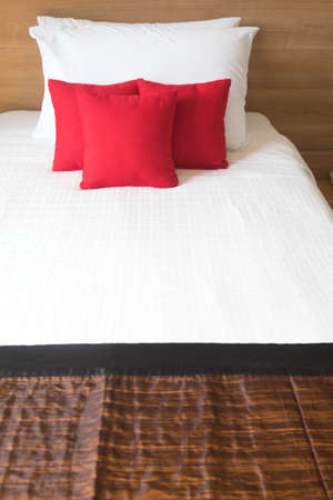 red pillows: Red pillows on white bed in bedroom Stock Photo