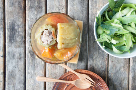 Stuffed bitter gourd with minced pork and carrot in clear soup on wood table Stock Photo