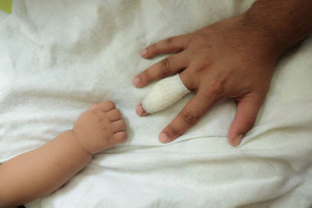 misadventure: concept of love and family. injury hand finger take care by baby