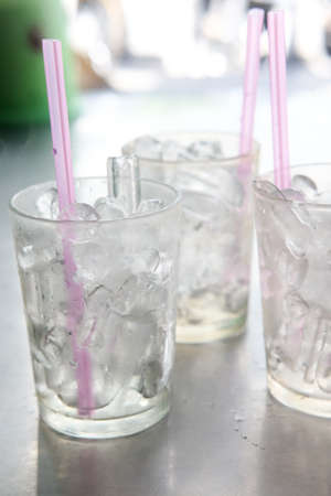 vasos de agua: Ice in glass with straw on table