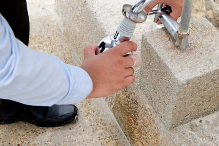 businessman opening water tap at outdoor office