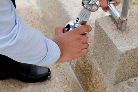 misadventure: businessman opening water tap at outdoor office