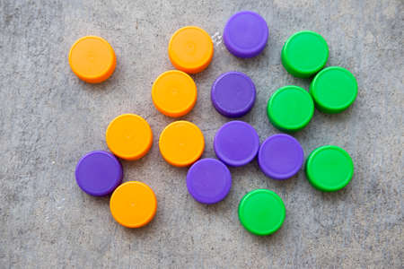 segregation: group of multicolored bottle caps, green, orange and violet Stock Photo