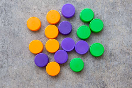 ornage: Orange, violet and green plastic bottle caps, top view