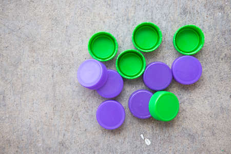 Green and violet  plastic bottle screw caps, top view