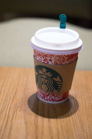 Bangkok, Thailand - December 31, 2016 : Starbucks paper cup take away have images christmas on a red cup.place on wooden table