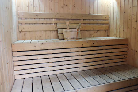finnish bath: Bucket for water and pillows on bench in finnish sauna. Stock Photo