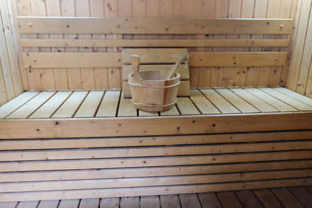 finnish bath: Bucket for water and pillows on bench in Finnish sauna.