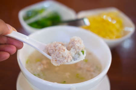 Close up minced pork on white spoon soft boiled rice, Thai style breakfast with pork