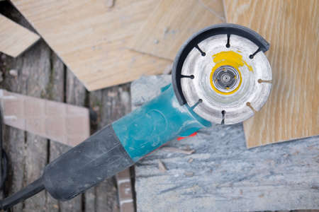 industrial tool hand grinder cutting marble on construction site Stock Photo