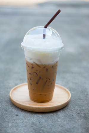 Iced coffee with straw on saucer in plastic cup at coffee shop Stock Photo