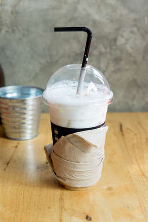 Iced coffee latte in takeaway cup on wood table