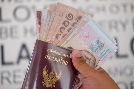 Tourist hold passport and Thai money, travel concept Stock Photo