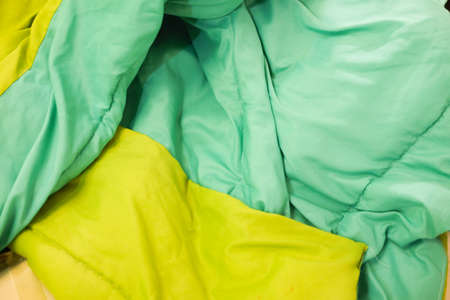 unmade: Green duvet and on an unmade bed