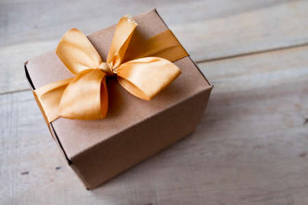 Brown paper wrapped gift box with golden bow Stock Photo