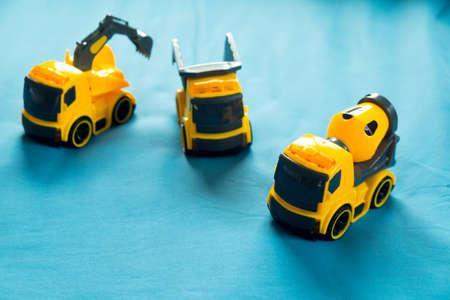 Three yellow toy  Industrial Vehicle on blue bed, Childrens construction machinery
