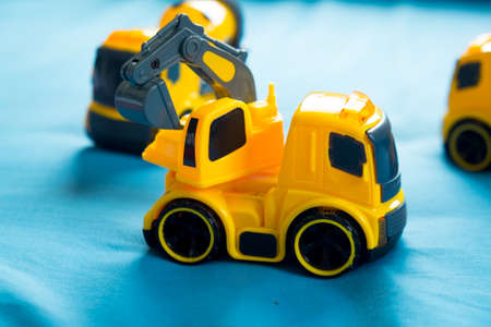 Childrens toy yellow tractor on blue background Stock Photo