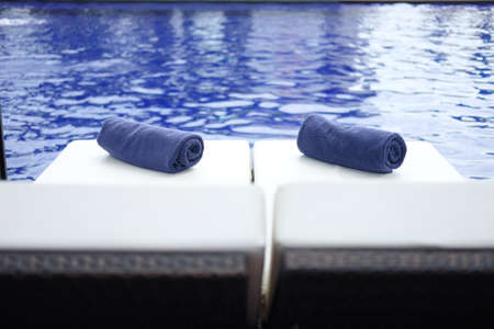 Towel roll on sunbeds at swimming pool