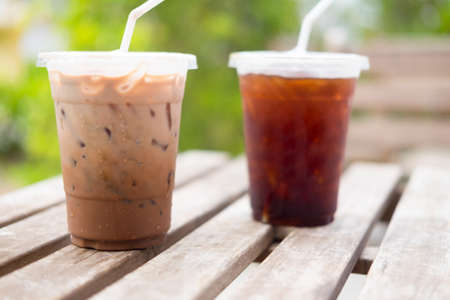 Iced coco and ice black coffee with straw in plastic cup on wood table