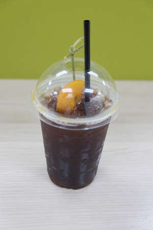 Black coffee with peach (Fusion drink) on wood table