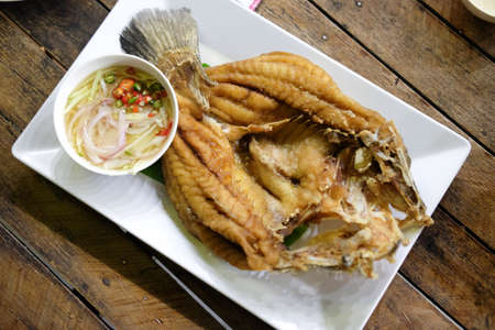 Fried snapper with fish sauce and spicy salad on white dish, top view Stock Photo