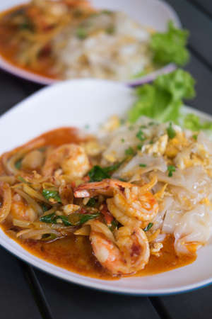 Stir rice noodle roasted chicken is delicious with Tom Yum Kung a Thai traditional spicy prawn soup (Thai Fusion food) Stock Photo
