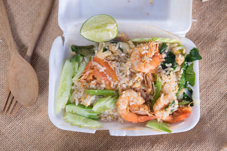 Fried rice with prawn herbs and vegetables in foam box, top view Stock Photo