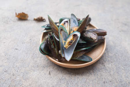 Close up of appetizing fresh steamed mussels on wooden dish