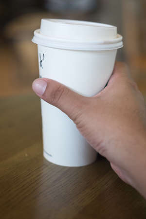 Mans hand holding white empty paper coffee cup on wood table