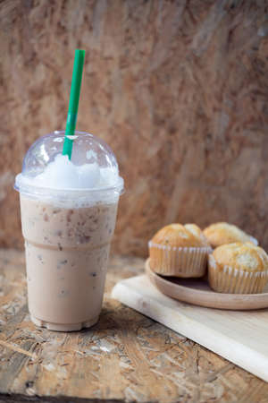 Ice coffee and banana muffin on wooden table Stock Photo