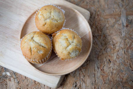 Fresh delicious homemade banana cup cakes on wooden dish