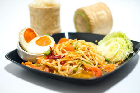 Som tum Thai with sticky rice and salted egg in black dish Stock Photo