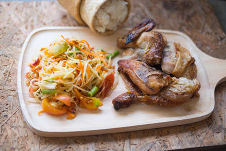 Spicy papaya salad grill chicken and sticky rice served on wood tray