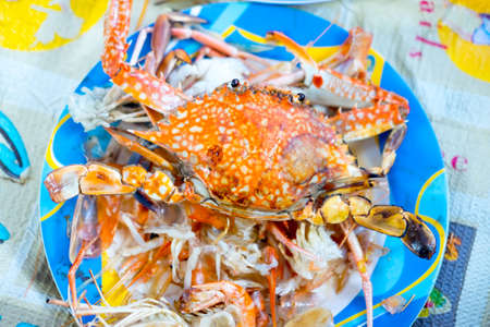 Grilled big red crabs on blue plate.