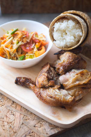 Grill chicken and sticky rice served with spicy papaya salad Stock Photo