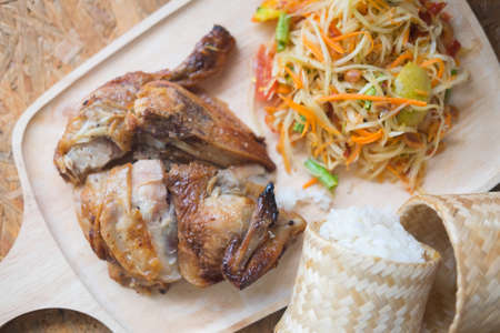 Famous Thai food papaya salad and grilled chicken with sticky rice on wooden plate, selective focus